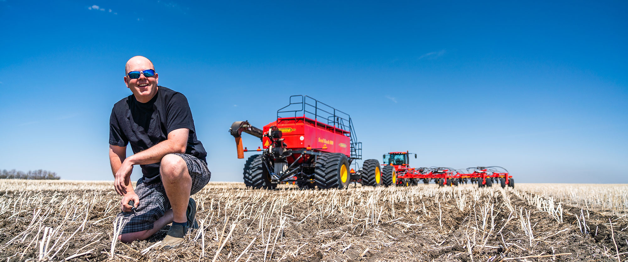 Farmer in front of Seed Hawk machines